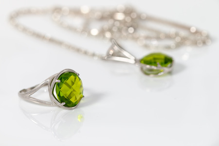 Beauty silver ring and pendant with olivine on white acrylic desk. Archivio Fotografico