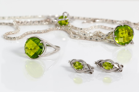 Close-up beauty silver earrings, ring and pendant with peridot on background chain and ring on white acrylic desk.