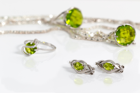 Close-up beauty silver earrings and small ring with peridot on background pendant, chain and big ring on white acrylic desk.