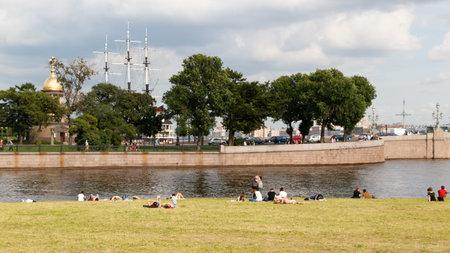 ST PETERSBURG, RUSSLAND - 18. AUGUST 2017: Leute, die auf den Banken des Neva River bei St- Peter- und Paul-Festung auf dem Hintergrund der Kirche der Kapelle der Heiligen Dreifaltigkeit und der Masten der Fregatte ein Sonnenbad nehmen.