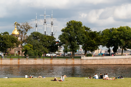 SAINT PETERSBURG, RUSSIA - AUGUST 18, 2017: People resting on the banks of the Neva River at the Peter and Paul Fortress on the background of the Church of the Holy Trinity, chapel and the masts of the Frigate.