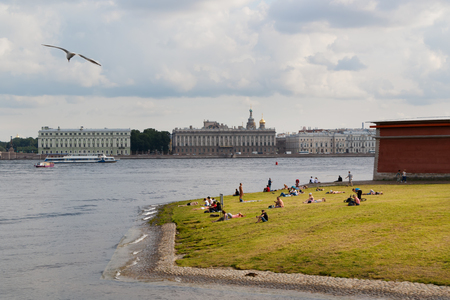 SAINT PETERSBURG, RUSSIA - AUGUST 18, 2017: People resting on the banks of the Neva River at the Dvortsovaya embankment.