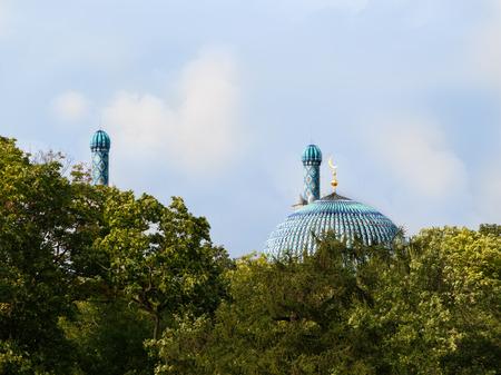 Hauptkuppel und Minarett von St- Petersburgmoscheus hinter den Bäumen auf einem bewölkten Himmel des Hintergrundes