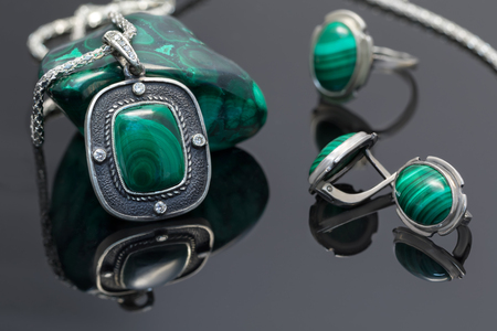 Closeup vintage silver pendant and earrings  with malachite on background of silver ring and piece of malachite on black acrylic board. Stock Photo