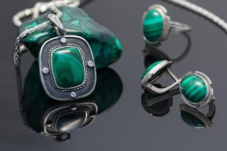 Silberner Anhänger der Nahaufnahmeweinlese und Ohrringe mit Malachit auf Hintergrund des silbernen Ringes und Stück Malachit auf schwarzem Acrylbrett.