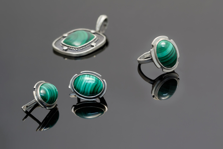 Closeup beauty silver earrings and ring with malachite on background of pendant on black acrylic desk.