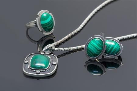 Silberner Anhänger der Nahaufnahmeweinlese, Ohrringe und Ring mit Malachit auf schwarzer Acrylplanke.
