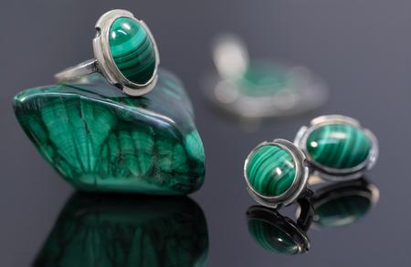 Silberne Ohrringe und Ring der Nahaufnahmeschönheit mit Malachit auf Malachitsteinstück auf schwarzem Acrylschreibtisch. Standard-Bild