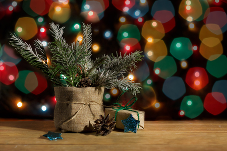 Christmas tree in pot and  gift box in wrapping paper, stars and pinecone on background of lights garland Standard-Bild - 89993825