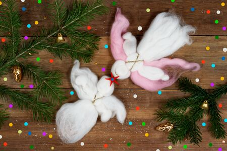 Christmas card: two white woolen angels, red star, colorful confetti and evergreen branches on wood plank. Standard-Bild