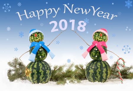 Karte mit zwei Wassermelonen Schneemann auf blauem Hintergrund und fallenden Schneeflocken. Feiertagskonzept für neue Jahre mit Aufschrift 2018 Standard-Bild