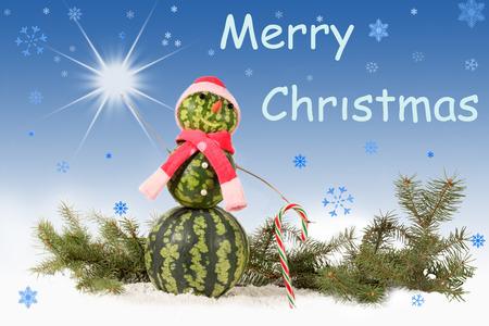Gemacht von der Wassermelone Schneemann im roten Hut und im Schal mit Zuckerstange auf blauem Hintergrund und fallenden Schneeflocken. Feiertagskonzept für Weihnachten mit Aufschrift und Stern Standard-Bild - 90815831