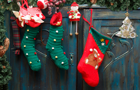 Christmas decorations: red Santas boot, green stockings, evergreen branch with pine cones and christmas toys on blue doors of old wardrobe.