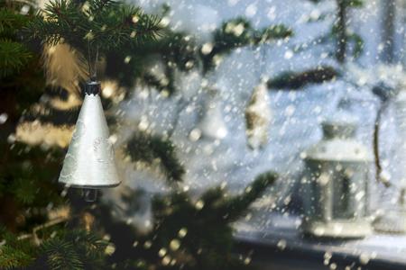 Plastiksilberfarbene Glocke auf einem immergrünen Baum auf einem Hintergrund von einem Schneien und von einer Lampe auf einem Portal. Kleiner DoF-Fokus setzt nur auf Glocke. Retro-Stil Standard-Bild - 91436779