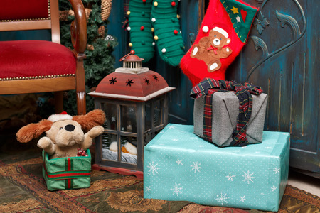 Christmas decorations: gift boxes, lamp, red boot, green stockings on the carpet near blue  old wardrobe and brown chair.