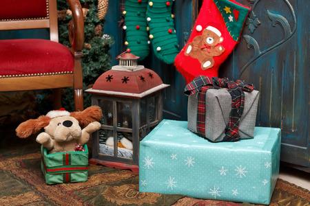 Weihnachtsdekorationen: Geschenkboxen, Lampe, roter Stiefel, grüne Strümpfe auf dem Teppich nahe blauer alter Garderobe und braunem Stuhl. Standard-Bild - 91301144