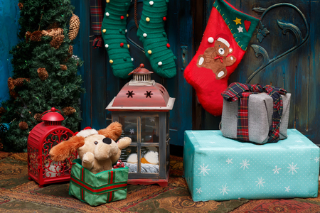 Christmas decorations: gift boxes, lamps, red boot, green stockings on the carpet near blue old wardrobe and small fir. Standard-Bild