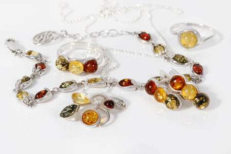 Close-up beauty silver pendant, earrings, rings and bracelet with different colors baltic amber on white acrylic desk.