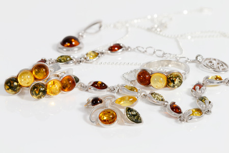 Closeup of beauty silver pendants, earrings, ring and bracelet with different colors baltic amber on white acrylic desk. Stock Photo
