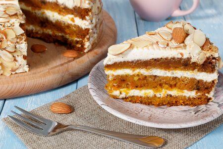 Nahaufnahme des vegetarischen Karottenkuchens mit Mandeln auf einer Untertasse, einer Gabel und einem Holzbrett mit Kuchen in der Nähe auf blauem Holztisch. Rosa Tasse im Hintergrund.