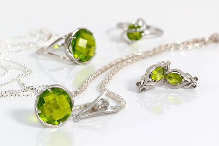 Close-up beauty silver earrings and pendant with peridot on background  chain and rings on white acrylic desk. Banque d'images