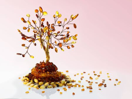 Decorative tree made with yellow and dark brown baltic amber, amber beads and small pieces of raw amber on white acrylic surface on pink gradient background