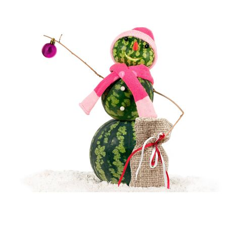 Watermelon christmas snowman in pink hat and scarf in the snow with christmas balls and linen gifts sack.  Holiday concept for Christmas.