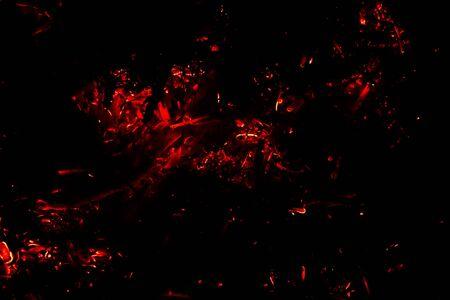 fliegende glühende Funken auf schwarzem Hintergrund/das Konzept der Brandgefahr