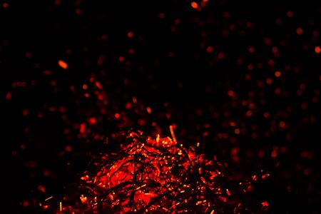 Close-up dying fire and hot red sparks on a black background