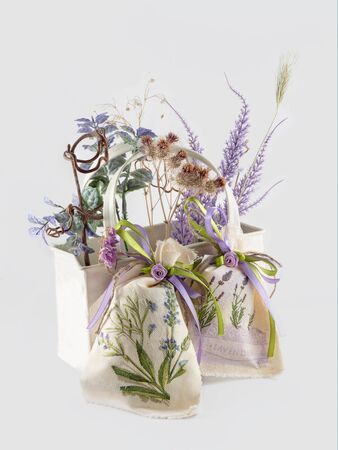 the dried flowers in white basket and two handmade linen sacks on white background