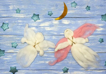 two woolen flying angel dolls, stars and lunar month on blue wooden background