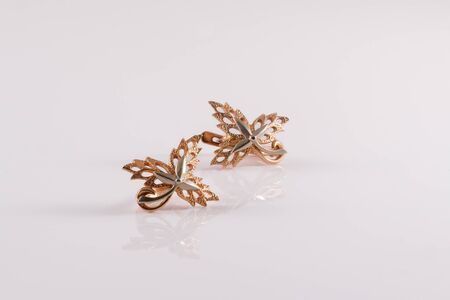 Close-up gold earrings in the form of maple leaves embellished with platinum