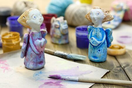 Paintbrush, paint in jars and handmade figurines