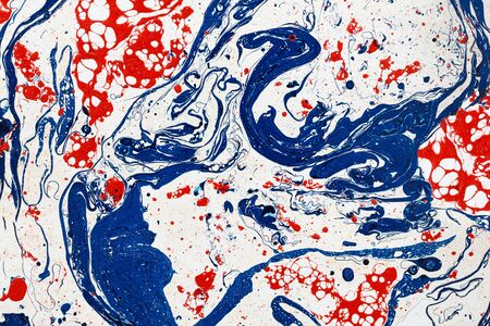 Abstract paint splash on paper as creative background. Mixing blue and red paints. Drops.  Liquid paint. Imagens