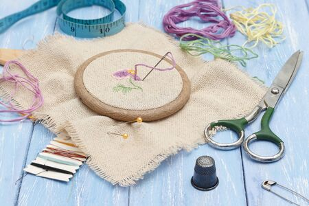 Thread and linen fabric in the wooden embroidery frame for needlework, scissors, thimble and  sewing meter on blue wooden table. workplace for sewing and embroidery. Imagens - 144551625