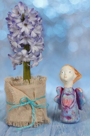 Greeting card with handmade clay angel and hyacinth flower in pot on blue wooden table on bokeh background. Valentine's day, wedding, easter or birthday concept. Imagens
