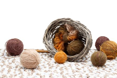Colorful yarn in tangle and coil  in overturned braided basket, near   tangles of yarn  and wooden spokes. isolated on white background Imagens - 144823725