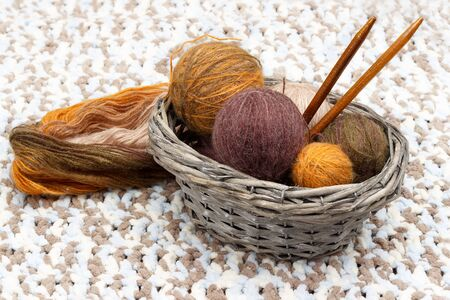 Colorful yarn in balls and needles lies in braided basket, near  coil of yarn Imagens