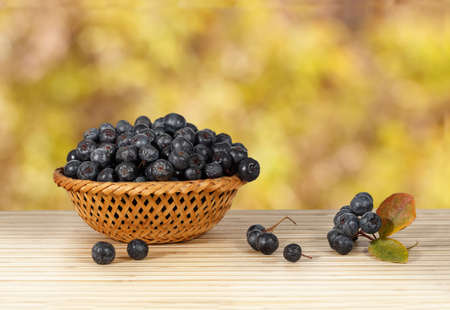 Close-up of chokeberry in a wicker basket on a wooden table on a background yellow leaves