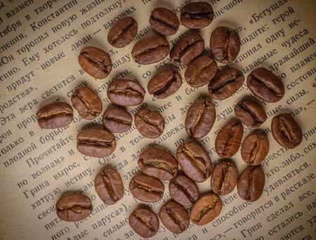 Composition of coffee beans on the page of an old book close-up.