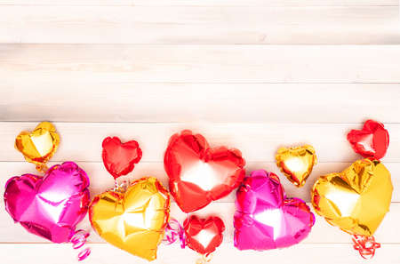 nine foil pink, red and golden balloons in the shape of a heart with ribbons on a white and beige wooden background. Valentine's Day. The 14th of February concept. banner with copyspace. place for text. flatlay