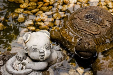 Clay doll of turtle and boy in pond