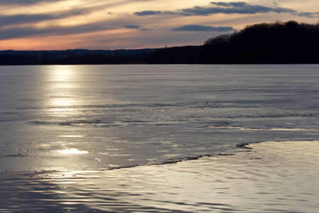 rural skyline: Image with a beautiful sunset on the icy lake and the forest