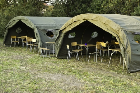 two big military tents in forest