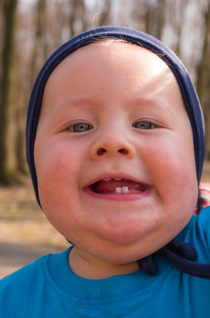 laughing little boy shows his two milk teeth Stock Photo