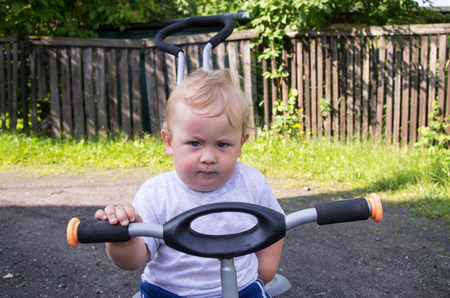 Little blond boy sitting on a tricycle photo