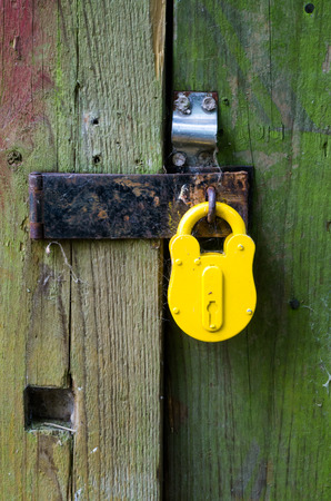 old yellow padlock on the door photo