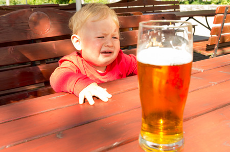 little boy crying seeing a glass of beer