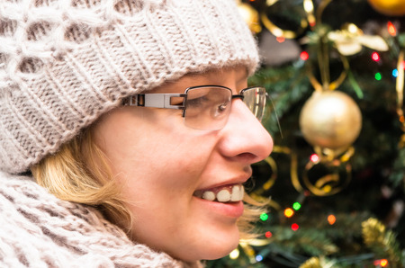 pretty blond woman wearing a hat and scarf on the background of Christmas tree photo
