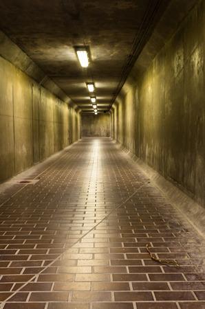 Dark corridor, lit a few lamps, mysterious and dangerous place photo